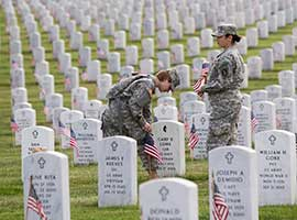 Staff Sgt. Kerrin Kampa of Mifflinburg, Pa., and Staff Sgt. Judy Dukes of Aurora, Ill., plant U.S. flags at Arlington National Cemetery in Virginia on May 23, 2013 in honor of the fallen to mark Memorial Day. CNS photo/Nancy Phelan Wiechec